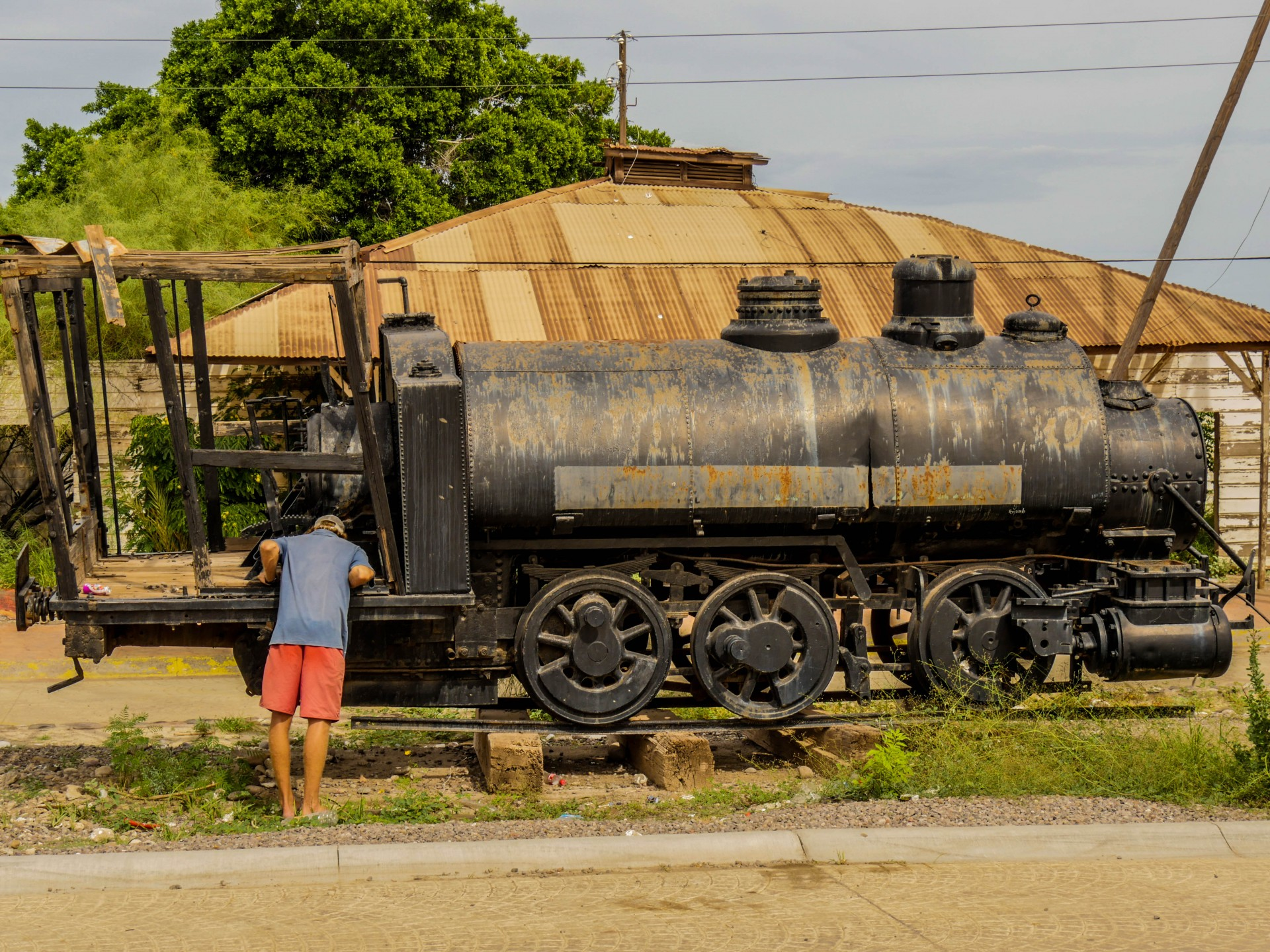 Josh peers into the narrow gauge rail engine on a side street in Santa Rosalía.