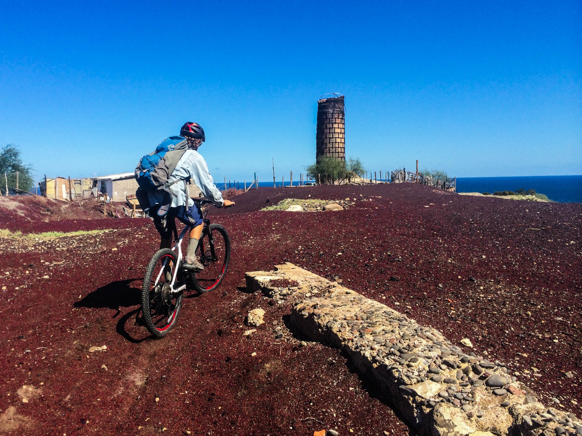 Josh rides out onto the top of the tailings pile, with the brick smokestack from the mine smelter in the background.